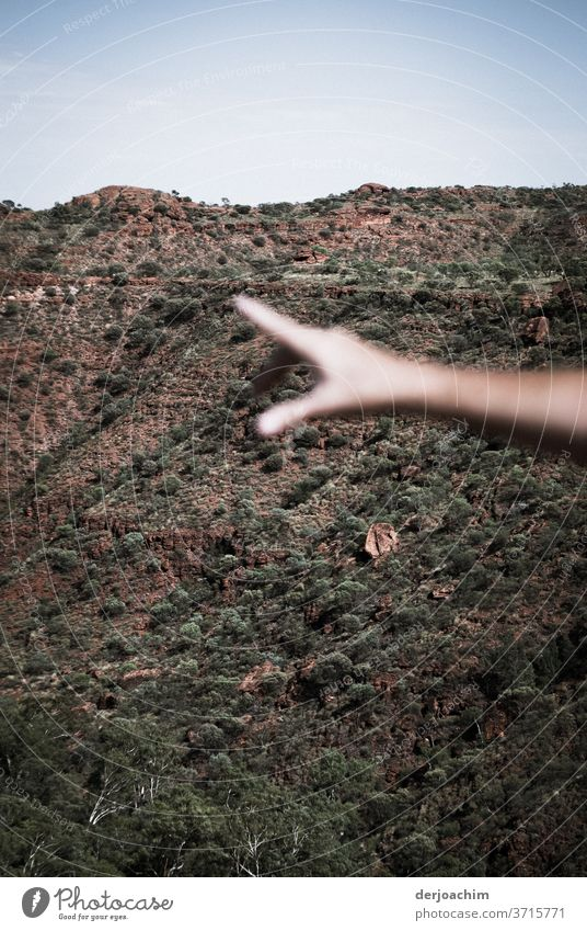 Da drüben zeigt die ausgestreckte Hand im Halbrund des Tales  auf etwas. Im Hintergrund ein felssiger Hang hand aufhalten Farbfoto Zusammensein Mensch