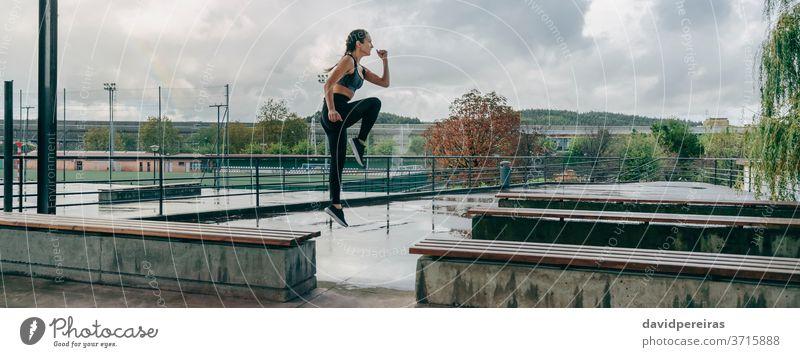 Mädchen springt beim Training auf Bänke regnerisch Sport springend Energie Ermächtigung Stil Körper Boxerflechten Fitness passen Transparente Netz panoramisch