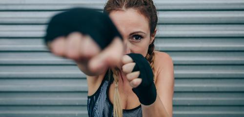 Sportlerin schaut in die Kamera und schlägt stark schauende Kamera schlagend Bowle Boxverband Ermächtigung Metallwand Training Boxerflechten Fitness Körper