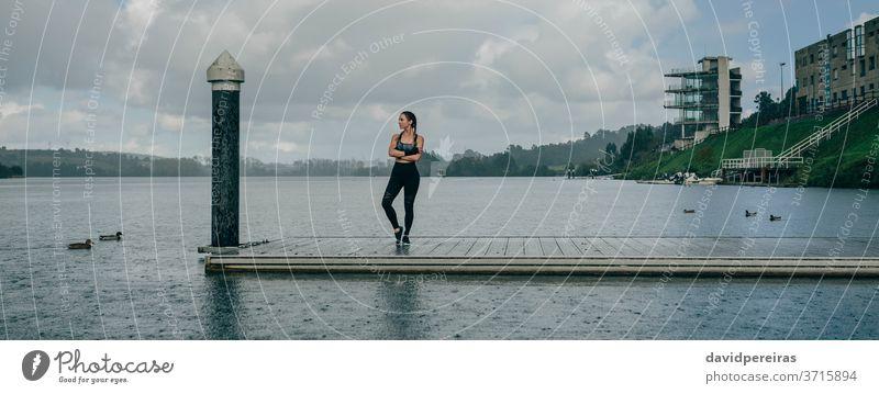 Sportlerin sieht den See vom Pier aus. Regen posierend verschränkte Arme Gelassenheit Boxerflechten Fitness passen Training regnet Mut Transparente Netz