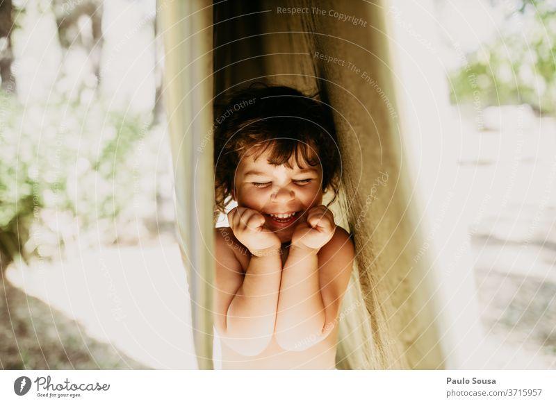 Mädchen amüsiert sich mit aufgehängter Kleidung Kind Kinderspiel Kindheit Kindheitserinnerung Kaukasier Spaß haben im Freien erhängen Wäscheleine Lifestyle