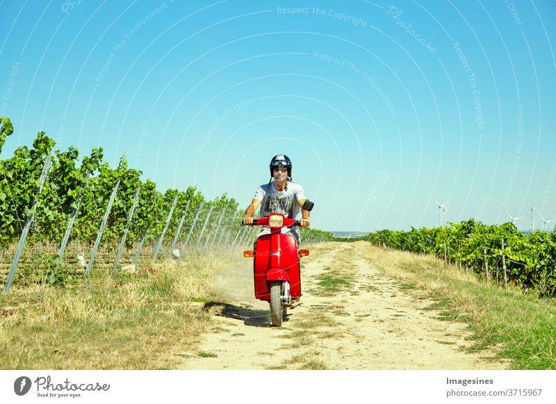 Roller im Weinberg fahren. Mann, mit Helm der Roller in der Landschaft fährt. Porträt eines Mannes und mit einem stilvollen Vintage-Moped im Sommer gegen blauen Himmel