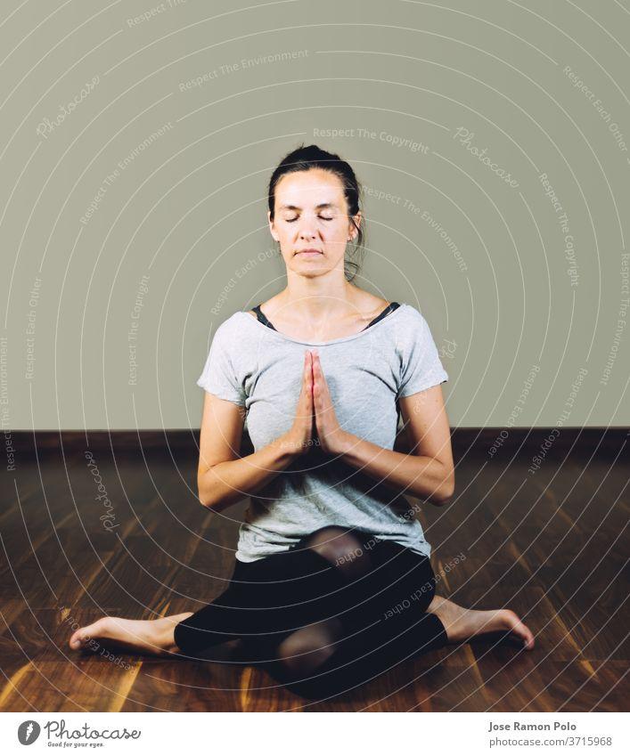 Frau sitzt im Schneidersitz auf dem Boden und macht Yoga-Entspannungsübungen. Konzept der gesunden Lebensweise und Yoga trainiert. Menschen meditierend Sitzen