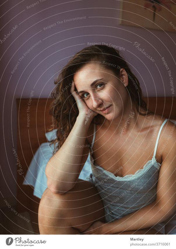 Angenehme Frau in Nachtwäsche, die morgens auf weichem Bett sitzend die Haare zerzaust und in die Kamera schaut Schlafzimmer im Innenbereich Erholung träumend