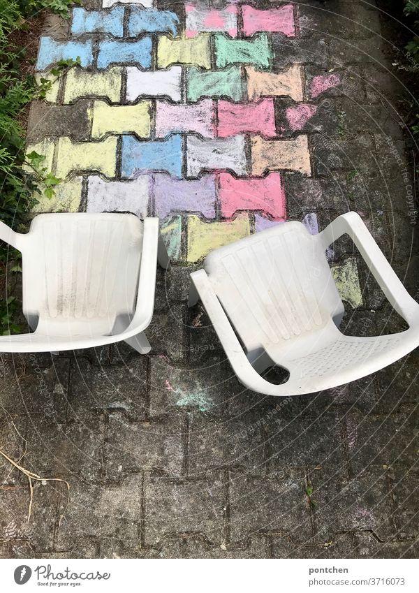 Zwei Gartenstühle aus Plastik für Kinder stehen vor einer bunten Malerei aus straßenkreide. Kinderspiel plastik kinderspiel straßenmalerei kreativität