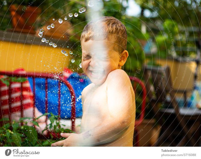 Junge wird auf der Terrasse mit Wasser bespritzt und lacht platschen spritzen Kind nackt Haut Garten Balkon Planschbecken Garten-Schleife Tropfen Wassertropfen