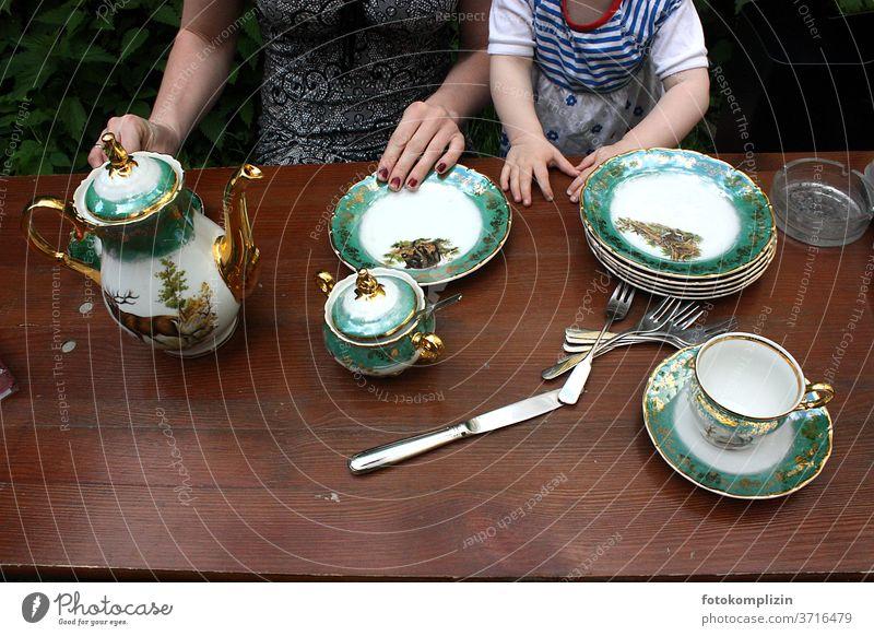 feines grün goldenes Porzellan Geschirr auf braunem Holz Tisch mit Blick auf Hände von Frau und Kind Porzellangeschirr Teller Tasse Keramik Kanne Kaffeekanne