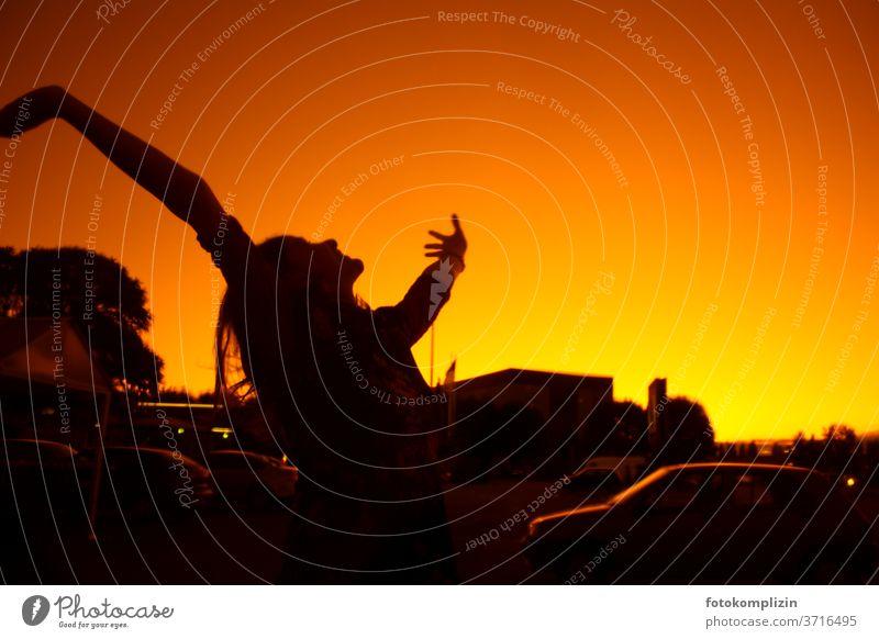 Silhouette einer Frau, die die Arme in den rotgelben Himmel streckt Glück Optimismus Freude Fröhlichkeit Bewegung Zufriedenheit Begeisterung Gefühle