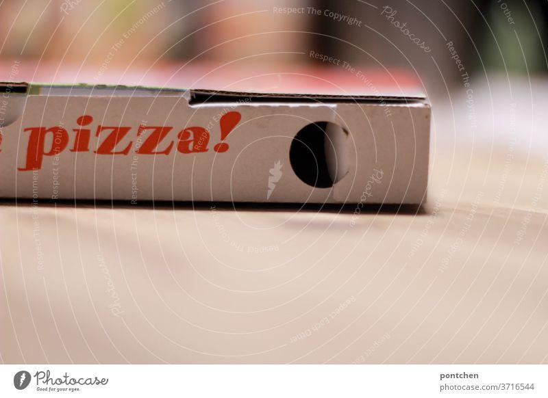 Das Wort Pizza steht auf einem Karton. Pizzakarton. Lieferdienst, Lieferservice lieferdienst pizzakarton zum mitnehmen bequemlichkeit essen bestellen tisch