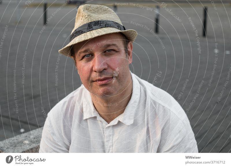 Ein Mann mit Hut schaut freundlich und etwas melancholisch in die Kamera Person Hemd Sommer Gesicht Kopf Portrait müde nachdenklich Mensch Blick maskulin