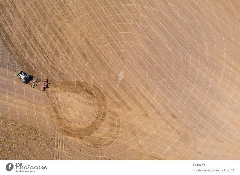 einen Traktor mit einem Pflug von oben Traktor von oben Feld Wiese Landwirtschaft Bauernhof trocknen Natur Erde trockene Erde Ernte Schlamm