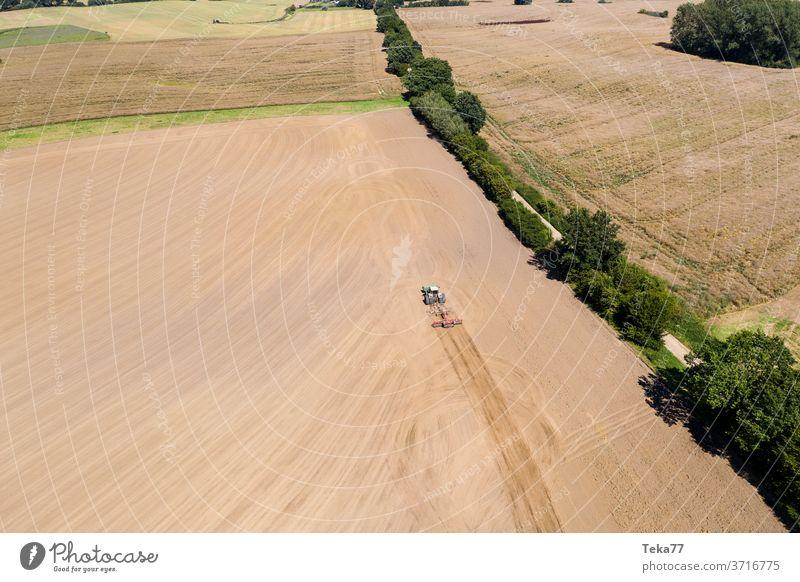 ein Traktor in einer Agrarlandschaft mit einem Pflug von oben Traktor von oben Traktor mit einem Pflug Feld Wiese Landwirtschaft Bauernhof trocknen Natur Erde