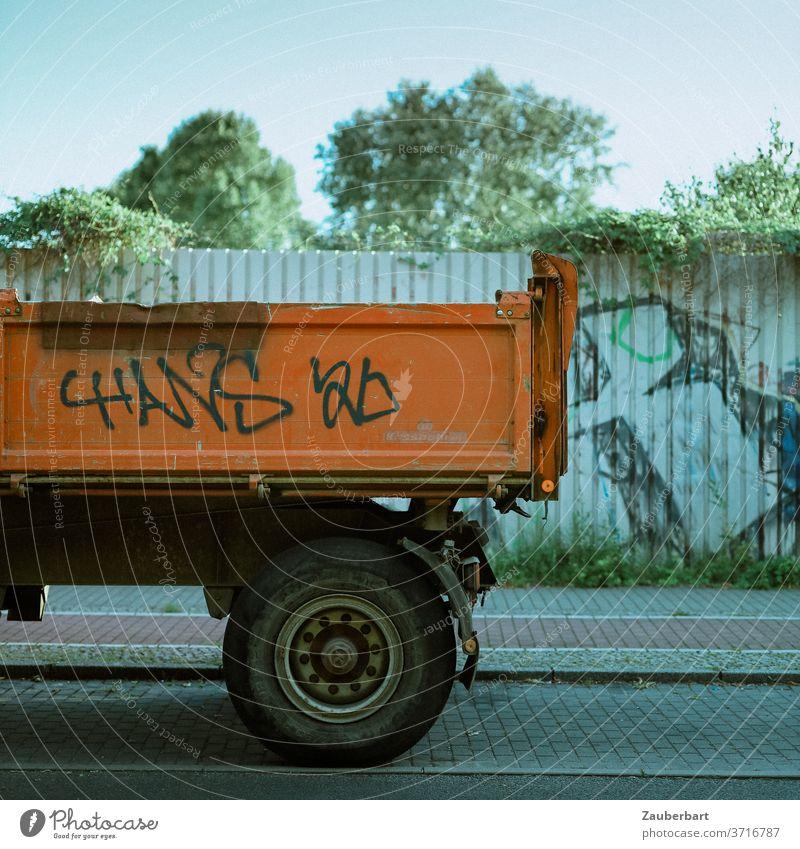 Ladefläche eines Lkw in Orange vor Wand aus Blech Lastkraftwagen Laster orange Räder Reifen Blechwand Zaun Grafitti Straße Pflaster Radweg Stand stehen