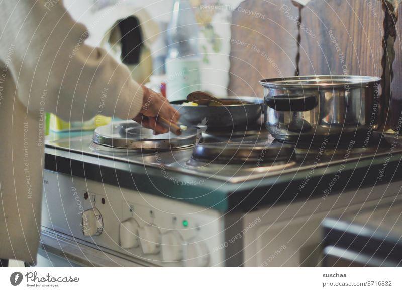 ältere frau steht am herd und bereitet ein essen zu Frau alt Herd stehen kochen Essen Essen zubereiten Herdplatte heiß Kochtopf Pfanne Schneidebretter Küche