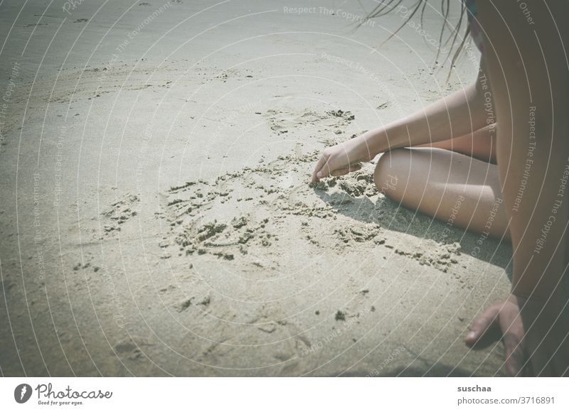kind sitzt an einem strand und malt mit dem finger ein bild in den sand Kind Kindheit Mädchen Strand Sand Sommer Sommerferien am Meer Urlaub malen spielen Küste