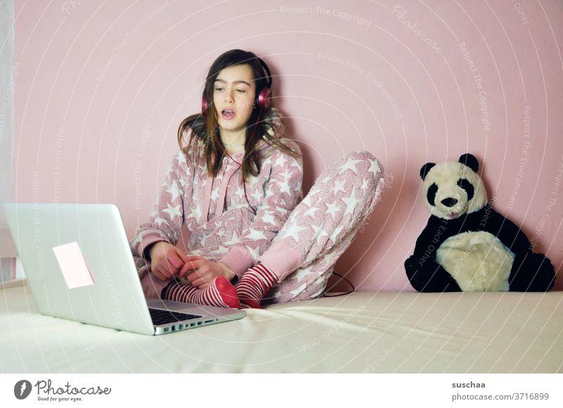 jugendliche sitzt vor ihrem laptop und hört musik oder chattet mit freunden. das pandabär-stofftier ist auch dabei .. Jugend Jugendliche Teenager Kind Mädchen