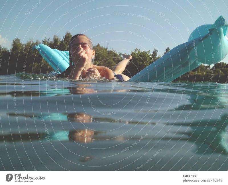 mädchen auf einer blauen luftmatratze an einem heißen sommertag am see kurz vor dem abtauchen Mädchen Kind See Badesee Wasser Luftmatratze schwimmen
