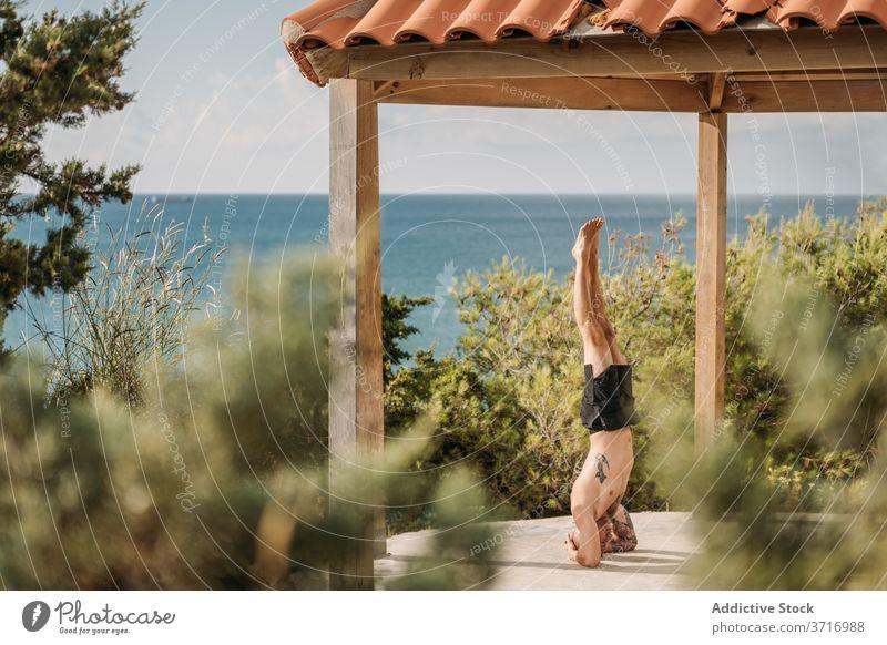 Starker Sportler beim intensiven Training calisthenics Übung Handstand Mann Gleichgewicht muskulös stark männlich Körper Fitness Kraft Athlet Gesundheit