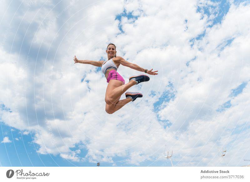 Sportlerin springt beim Training springen beweglich Frau Aktivität intensiv Lächeln Athlet Moment Energie Gesundheit Übung schlank Sportbekleidung über der Erde