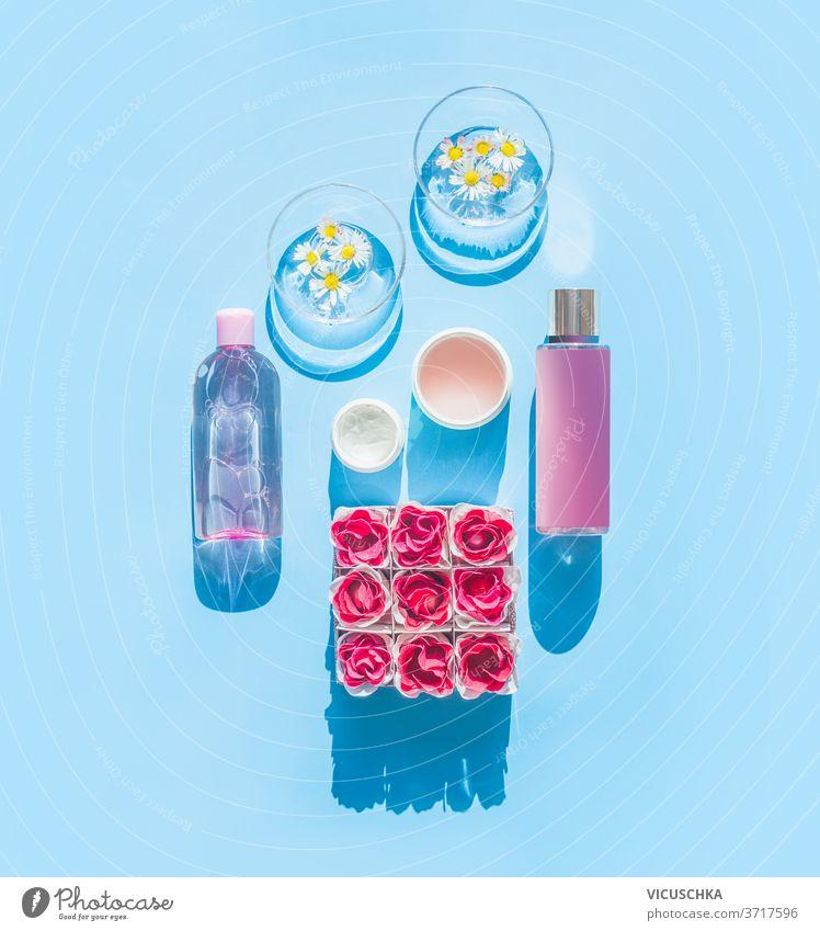 Zusammensetzung der natürlichen kosmetischen Produkte und Gläser mit Gänseblümchen, Flaschen, Tuben und Blumen auf hellblauem Hintergrund. Sommer-Hautpflege-Konzept. Ansicht von oben. Spa oder Wellness