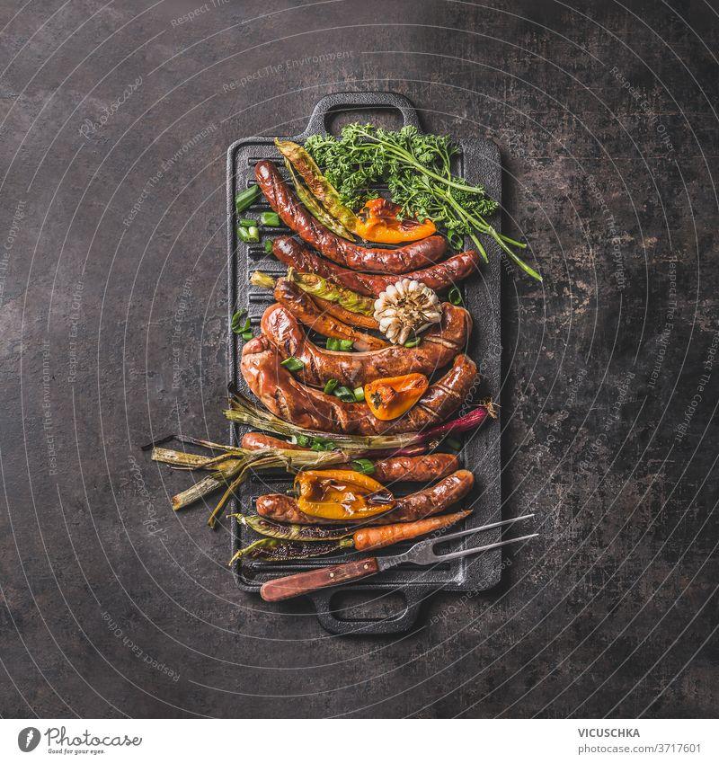 Grillwürste auf Gusseisenplatte. Ansicht von oben Bratpfanne gegrillt Lebensmittel gießen bügeln Teller Wurstwaren Paprika Frühlingszwiebel Knoblauch