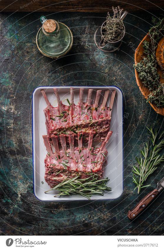 Rohe Lammrippchen mit Kräutern und Gewürzen auf einem dunklen, rustikalen Küchenhintergrund. Ansicht von oben. roh Lammrippen Küchenkräuter dunkel Hintergrund