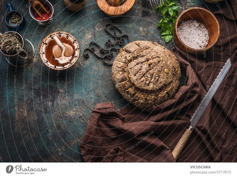 Hausgebackenes Vollkornbrot auf dunklem Küchentischhintergrund mit Messer und Kochwerkzeug selbstgemacht ganz Korn Brot dunkel Hintergrund Essen zubereiten