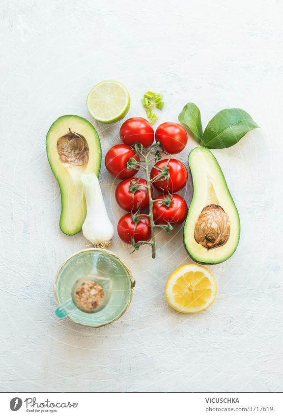 Frische Salatzutaten. Hälften von Avocado, Tomaten, Zitrone und Olivenöl auf weißem Hintergrund. Ansicht von oben. Vegetarisches Essen. Gesunde Ernährung frisch