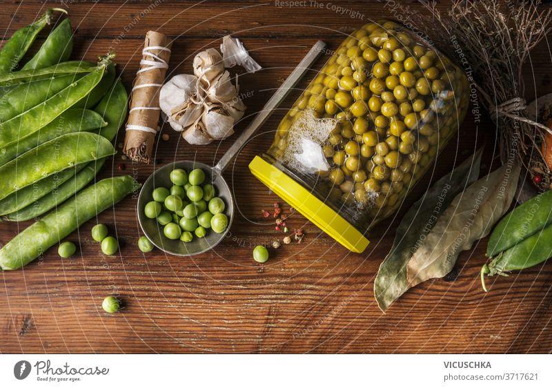 Konservierung von Gartengemüse. Einmachen von grünen Erbsen im Glas auf Holzuntergrund mit Zutaten. Ansicht von oben. Konzept der hausgemachten Konfitüre Gemüse