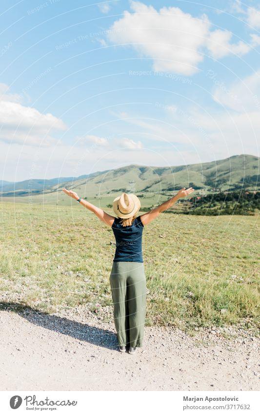 Junge weibliche Naturliebhaberin genießt im Sommer die Aussicht auf eine Bergkette Abenteuer Waffen schön sorgenfrei lässig genießend Europa erkunden Frau