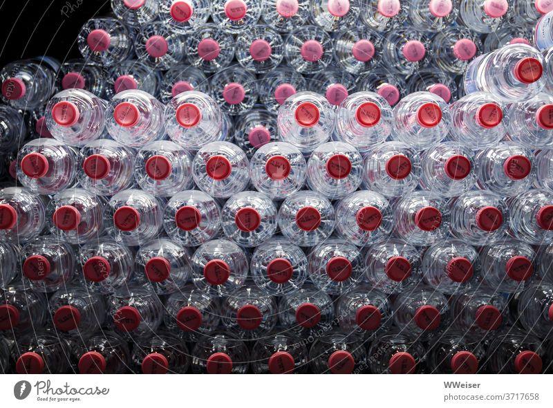 Viele Wasserflaschen liegen gestapelt in einem Kühlschrank zum Verkauf PET-Flasche Trinkwasser kühl viele kalt Kühlung Plastikflasche Deckel Beleuchtung Getränk
