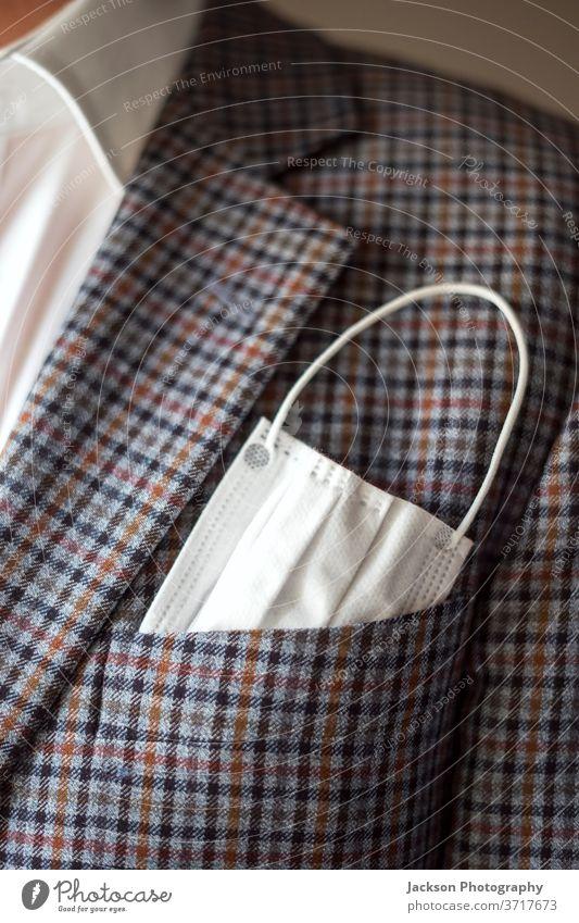 Eleganter Mann mit Schutzmaske als Taschentuch in der Brusttasche. Mundschutz Korona Jacke Einstecktuch Anzug Gesundheitswesen covid-19 Bund 19 COVID Pandemie