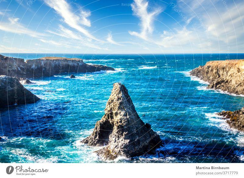 Kegelförmiger Felsen im Pazifischen Ozean unter blauem Himmel mit Wolken, Kalifornien Felsbrocken Landschaft reisen Uferlinie Strand Meer Zapfen Stein Wasser