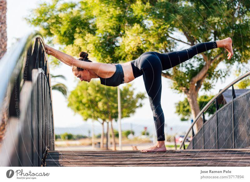 junge Frau bei Übungen auf einer Kupfer-Holzbrücke im Freien Yoga Natur Fitness Gesundheit Sport Pose hübsch Menschen Gleichgewicht beweglich gymnastisch