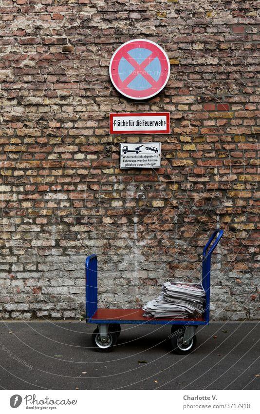 Hochkant im Halteverbot   Handwagen mit Zeitungen vor Ziegelwand mit Haltverbotsschild transportwagen zeitungen Zeitungsstapel Halteverbotsschild