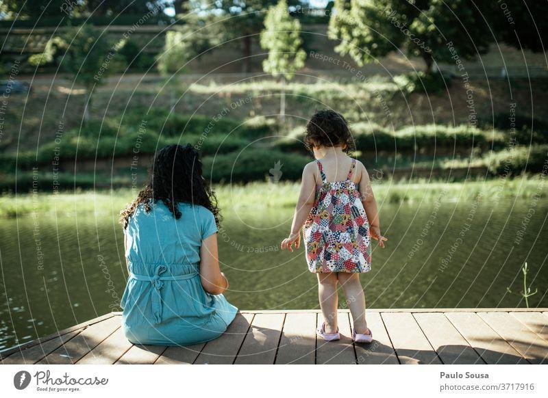 Mutter und Tochter schauen auf den Fluss Mutter mit Kind Mutterschaft Kindheit Zusammensein Fröhlichkeit Frau Pflege Menschen Liebe Eltern