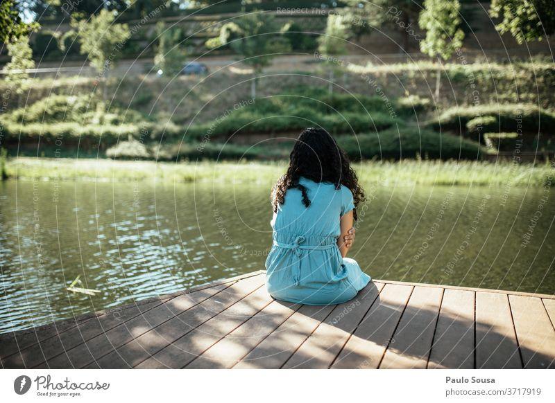 Rückansicht einer Frau auf dem Fluss Flussufer beschaulich zuschauend Einsamkeit allein einsam Liebeskummer Kaukasier Blick Denken schön Erwachsener Lifestyle