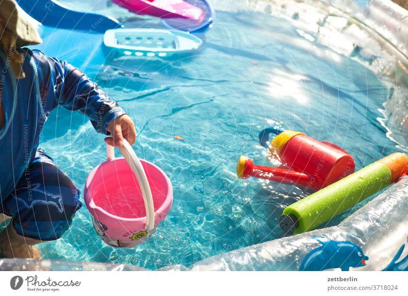 Kleines Kind im kleinen Swimmingpool pool swinningpool becken wasser wasserbecken planschbecken baden sommer hochsommer hitze spiel spielzeug wasserspielzeug