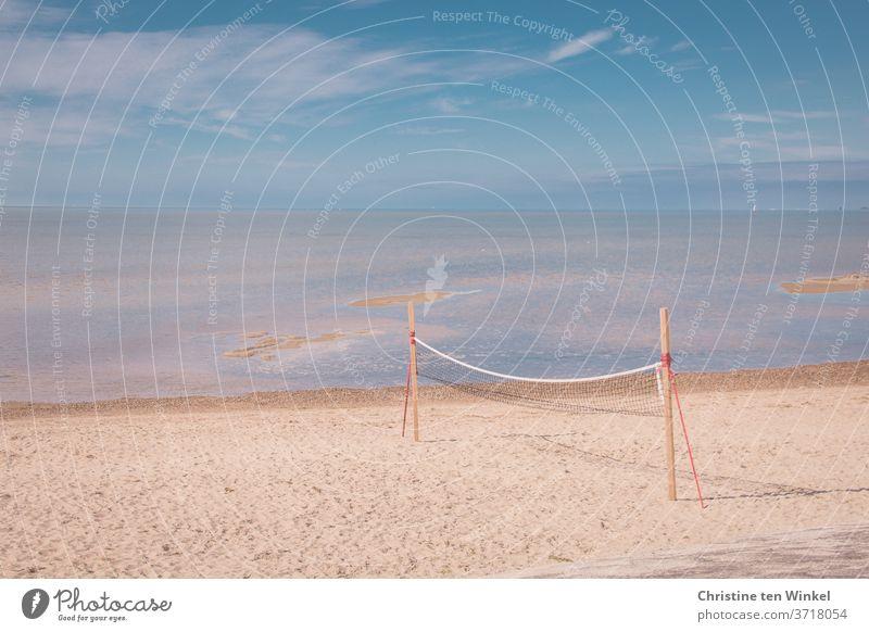 Leerer Nordseestrand mit Volleyball / Beachball Netz  direkt am Wasser. Sonnenschein, blauer Himmel, einige Wolken und Horizont. Strand Beachballnetz