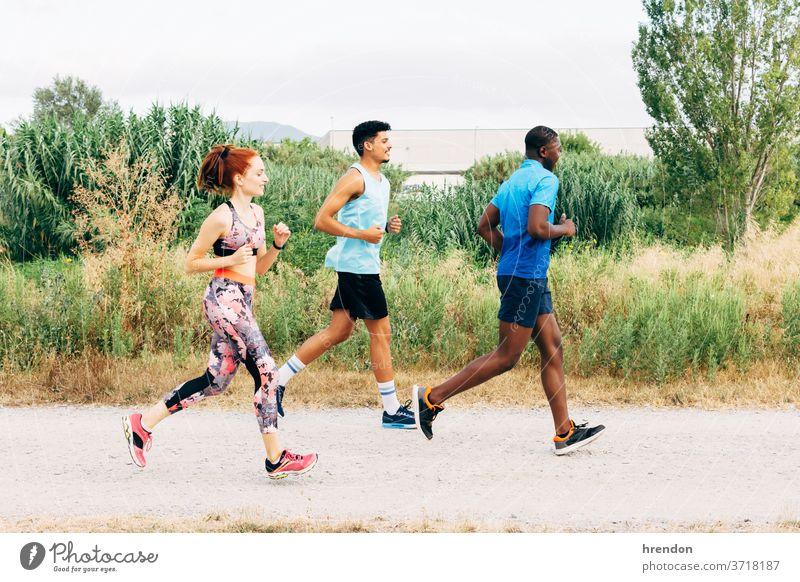Drei Freunde trainieren im Freien, laufen in ländlicher Umgebung Sport drei Personen rennen junge Männer Junge Frauen Athlet Vitalität Bewegung