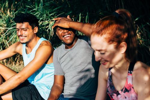 drei Freunde, die auf einer Bank sitzen, nachdem sie im Freien trainiert haben Freundschaft Sitzen Menschen trainiert. Sport Gesunder Lebensstil