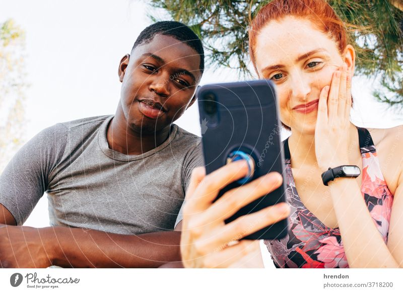 Freunde schauen auf das Smartphone, nachdem sie im Freien trainiert haben Freundschaft Gesunder Lebensstil Handy Frau Blick Fröhlichkeit junger Erwachsener
