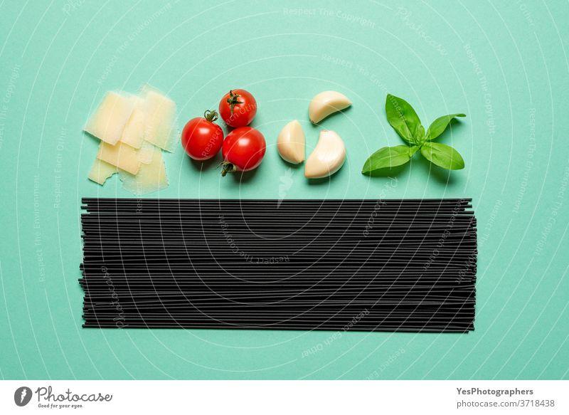 Schwarze Spaghetti und Saucenzutaten von oben gesehen. Ungekochte Nudeln isoliert auf grünem Hintergrund obere Ansicht ausgerichtet Basilikum schwarz
