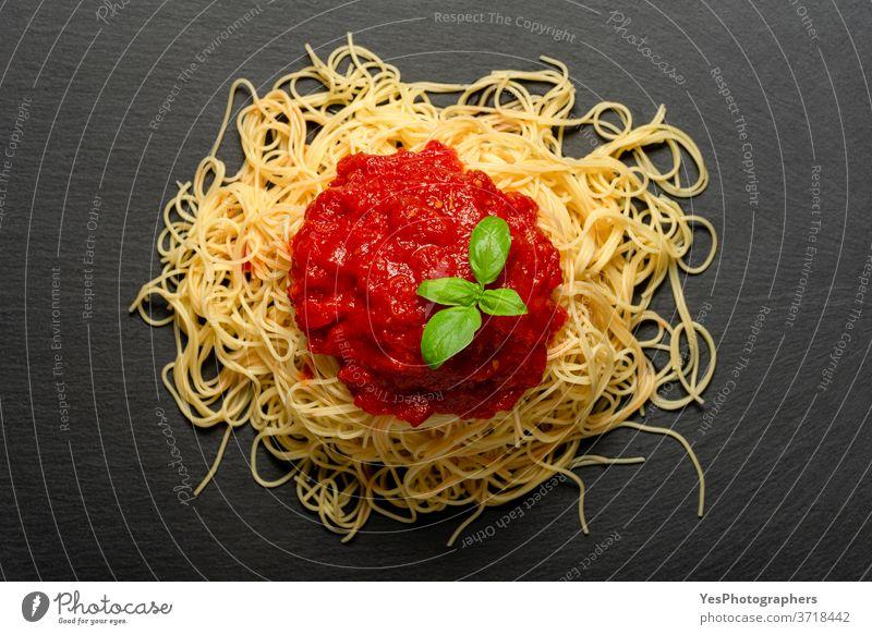 Spaghetti mit Tomatensauce auf einem schwarzen Granitteller. Gekochte Spaghetti mit roter Sauce. obere Ansicht Hintergrund gebacken Basilikum Kohlenhydrat