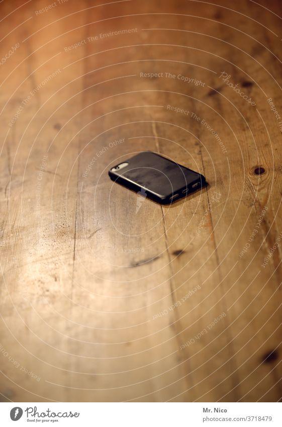 Ein Handy liegt auf dem Küchentisch und wartet auf den nächsten Einsatz Telefon Kommunizieren Technik & Technologie Telekommunikation Tisch Holztisch