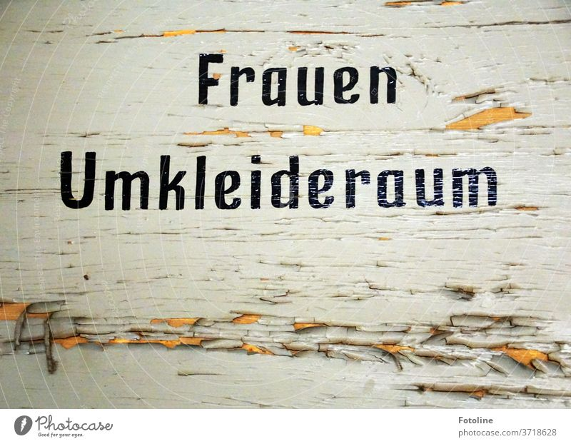 Frauen Umkleideraum steht an einer alten verfallenen Holztür, an der bereits die Farbe abblättert. Schrift Buchstaben Schriftzeichen Wort Text Typographie