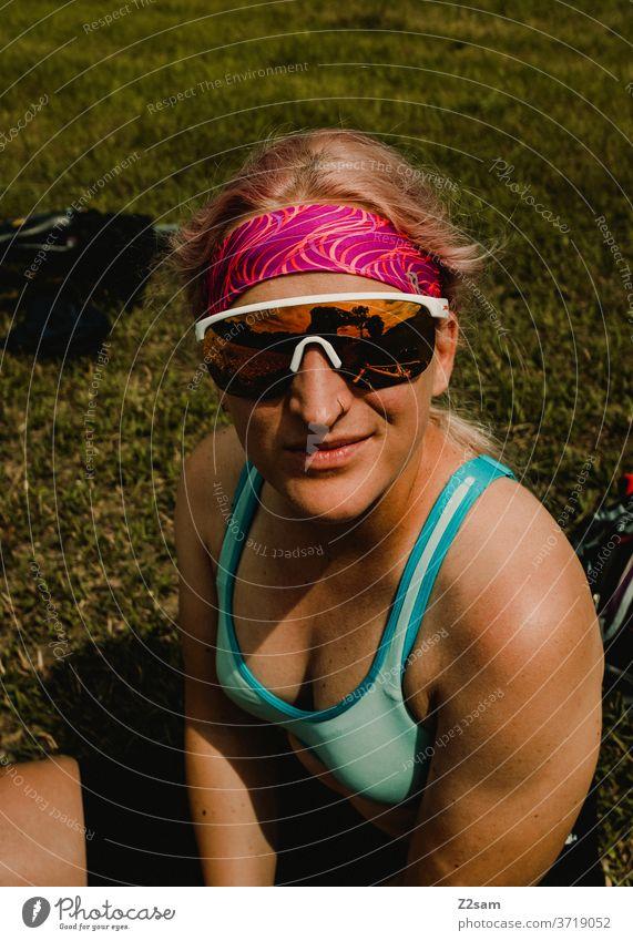 Sportliche junge Frau macht Pause sportler sportlerin junge frau mädchen top sportbekleidung sonnebrille stirnband braun haut körper athletin sommer wiese blond