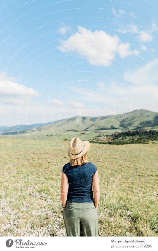 Junge weibliche Naturliebhaberin genießt im Sommer die Aussicht auf eine Bergkette Abenteuer schön sorgenfrei lässig genießend Europa erkunden Frau Freiheit