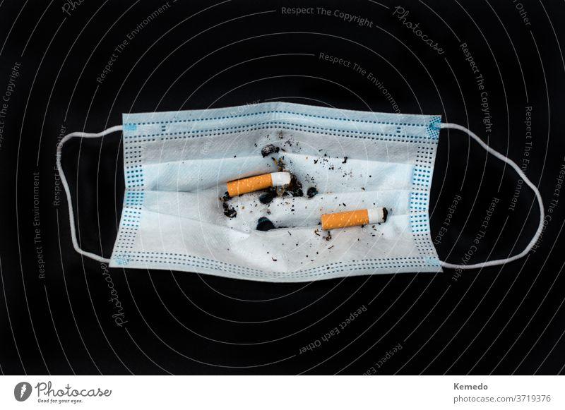 Gesichtsmaske mit Zigarettenstummeln als Aschenbecher, isoliert auf Schwarz. Mundschutz Coronavirus Bund 19 Korona Missbrauch neue Normale dumm Konzept Rauch