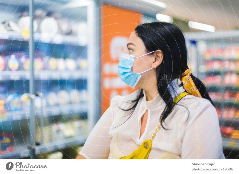 Lebensmitteleinkauf während COVID-19. Frau trägt eine schützende Gesichtsmaske und schaut beim Einkaufen in die Milchabteilung eines Supermarktes. Selektiver Fokus, Leerraum